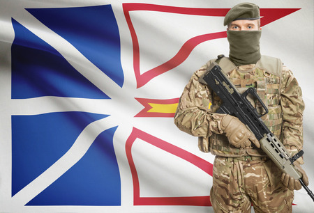 peacemaker: Soldier holding machine gun with Canadian province flag on background - Newfoundland and Labrador