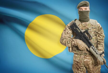peacemaker: Soldier holding machine gun with national flag on background - Palau