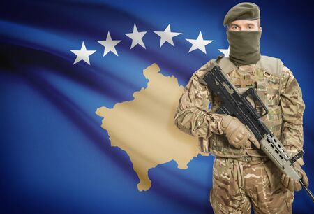 peacemaker: Soldier holding machine gun with national flag on background - Kosovo