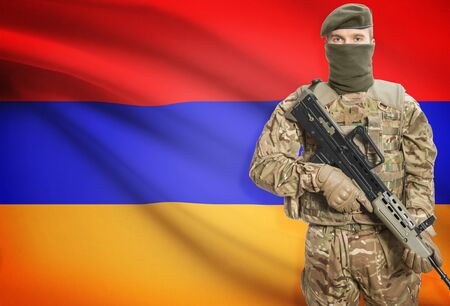 peacemaker: Soldier holding machine gun with national flag on background - Armenia