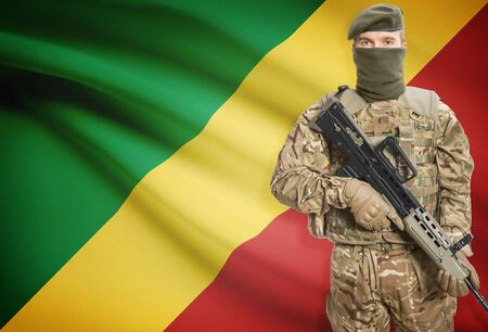 peacemaker: Soldier holding machine gun with national flag on background - Congo-Brazzaville Stock Photo