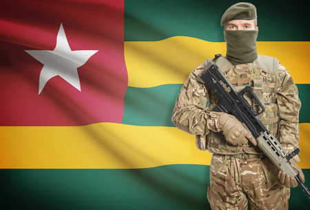 peacemaker: Soldier holding machine gun with national flag on background - Togo Stock Photo