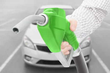methanol: Green fuel pump gun in hand with car on background Stock Photo