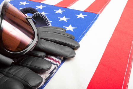 visions of america: Winter sport goggles and gloves over US flag - studio shot Stock Photo
