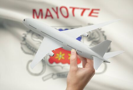mayotte: Airplane in hand with national flag on background - Mayotte