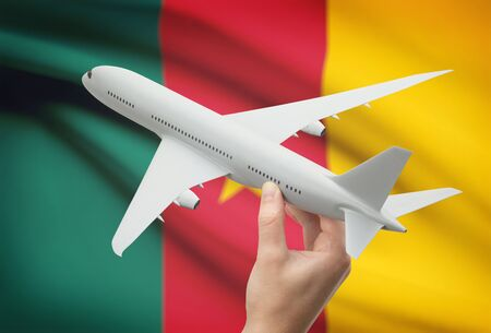 cameroonian: Airplane in hand with national flag on background - Cameroon