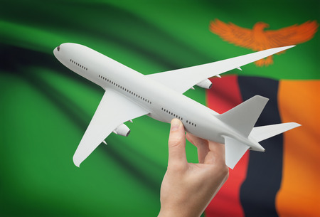 zambian flag: Airplane in hand with national flag on background - Zambia