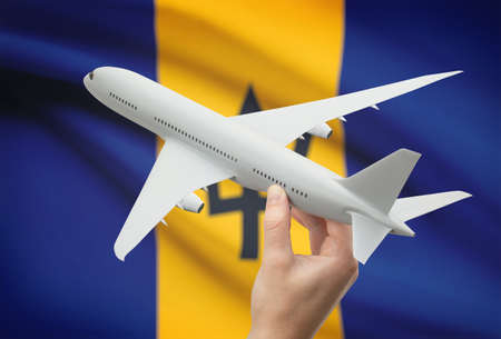 barbadian: Airplane in hand with national flag on background - Barbados Stock Photo