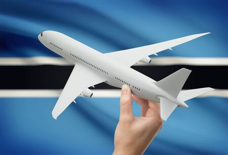 botswanan: Airplane in hand with national flag on background - Botswana