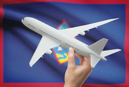 guam: Airplane in hand with national flag on background - Guam Stock Photo