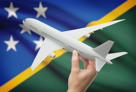 solomon: Airplane in hand with national flag on background - Solomon Islands Stock Photo