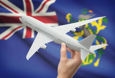 pitcairn: Airplane in hand with national flag on background - Pitcairn Islands