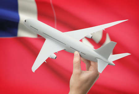 wallis: Airplane in hand with national flag on background - Wallis and Futuna