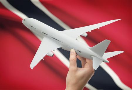 national flag trinidad and tobago: Airplane in hand with national flag on background - Trinidad and Tobago