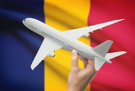 chadian: Airplane in hand with national flag on background - Chad