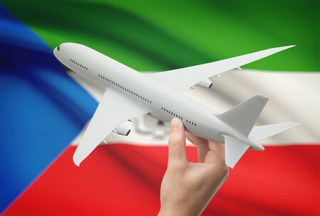 equatorial guinea: Airplane in hand with national flag on background - Equatorial Guinea Stock Photo