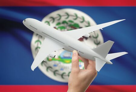 tourism in belize: Airplane in hand with national flag on background - Belize
