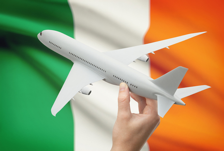 Airplane in hand with national flag on background - Ireland Фото со стока