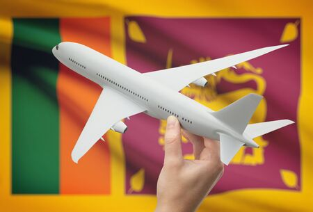 sri lankan flag: Airplane in hand with national flag on background - Sri Lanka