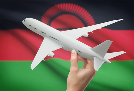 malawian flag: Airplane in hand with national flag on background - Malawi Stock Photo