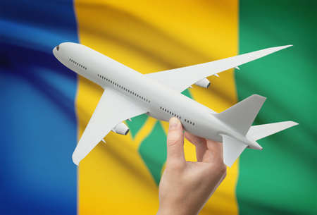 grenadines: Airplane in hand with national flag on background - Saint Vincent and the Grenadines