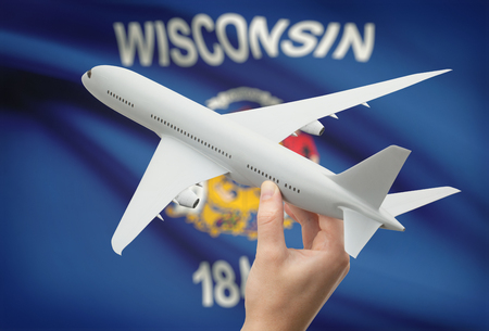 wisconsin flag: Airplane in hand with local US state flag on background - Wisconsin