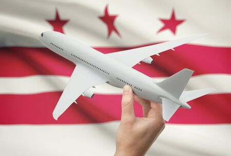 district columbia: Airplane in hand with local US state flag on background - District of Columbia