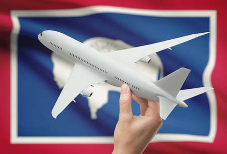 holiday budget: Airplane in hand with local US state flag on background - Wyoming