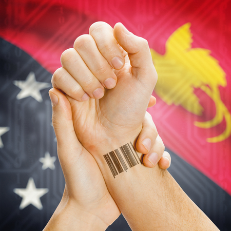 papua new guinea: Barcode ID number on wrist of a human and national flag on background series - Papua New Guinea Stock Photo