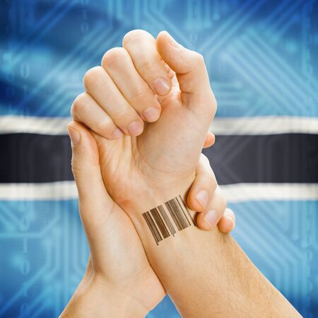 botswanan: Barcode ID number on wrist of a human and national flag on background series - Botswana