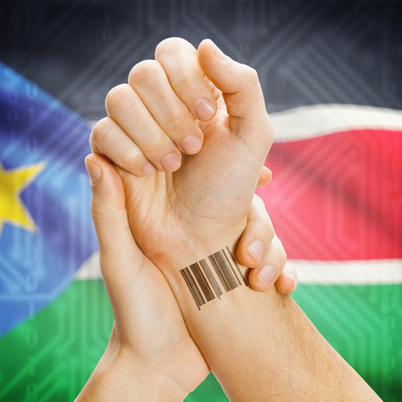 south sudan: Barcode ID number on wrist of a human and national flag on background series - South Sudan
