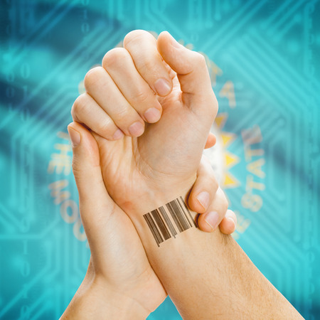breaking the code: Barcode ID number tatoo on wrist and USA statesl flag on background series - South Dakota Stock Photo