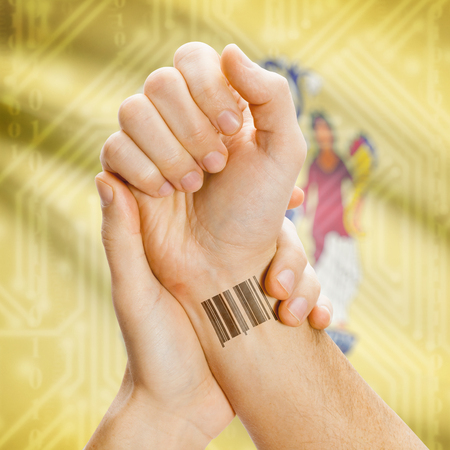 breaking the code: Barcode ID number tatoo on wrist and USA statesl flag on background series - New Jersey Stock Photo