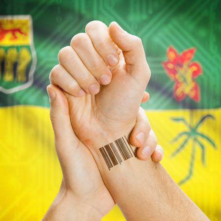 saskatchewan flag: Barcode ID number tatoo on wrist and Canadian province flag on background series - Saskatchewan Stock Photo