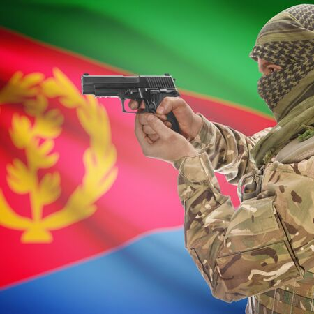 insurgency: Man with gun in hand and national flag on background series - Eritrea Stock Photo