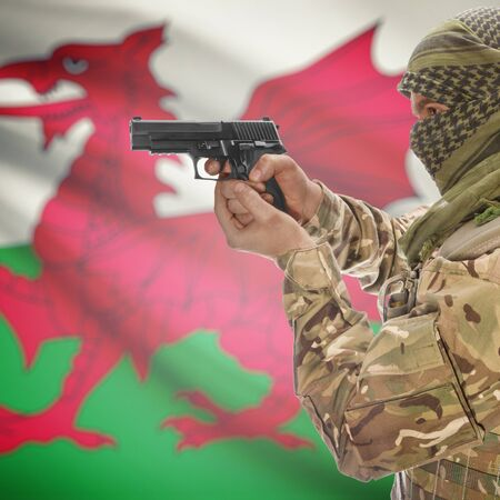 insurgency: Man with gun in hand and national flag on background series - Wales Stock Photo