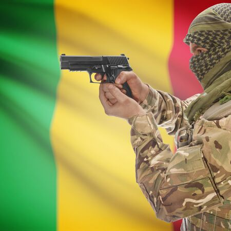 counterterrorism: Man with gun in hand and national flag on background series - Mali