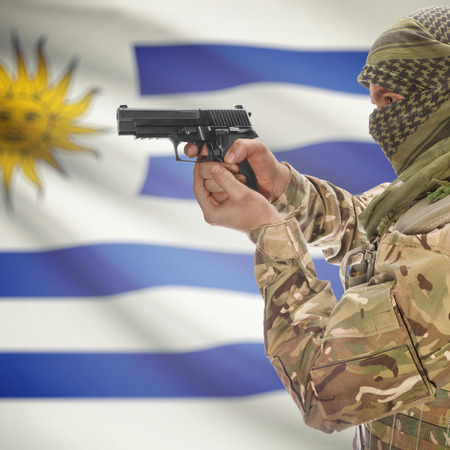 national police agency: Man with gun in hand and national flag on background series - Uruguay Stock Photo