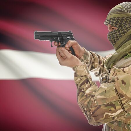 insurgency: Man with gun in hand and national flag on background series - Latvia