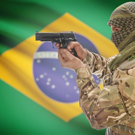 counterterrorism: Man with gun in hand and national flag on background series - Brazil Stock Photo