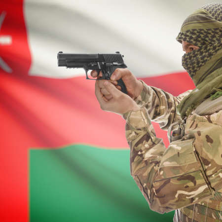 national police agency: Man with gun in hand and national flag on background series - Oman Stock Photo