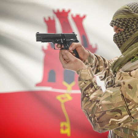 counterterrorism: Man with gun in hand and national flag on background series - Gibraltar Stock Photo