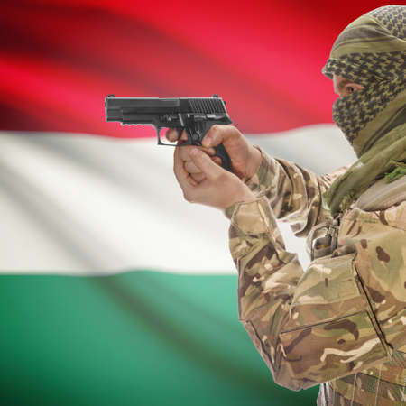 counterterrorism: Man with gun in hand and national flag on background series - Hungary