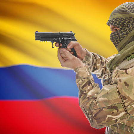 counterterrorism: Man with gun in hand and national flag on background series - Colombia