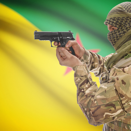 insurgency: Man with gun in hand and national flag on background series - French Guiana Stock Photo