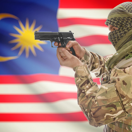 counterterrorism: Man with gun in hand and national flag on background series - Malaysia