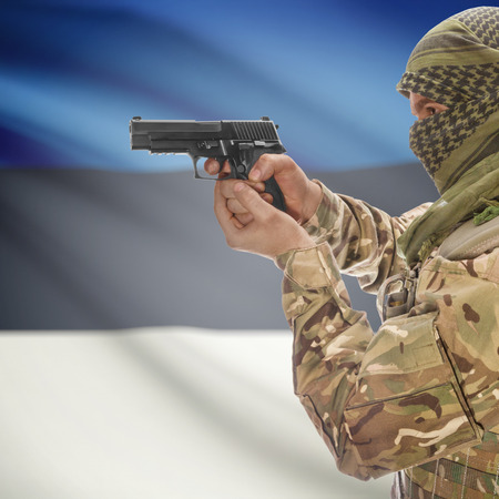 counterterrorism: Man with gun in hand and national flag on background series - Estonia Stock Photo