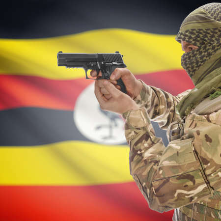 national police agency: Man with gun in hand and national flag on background series - Uganda