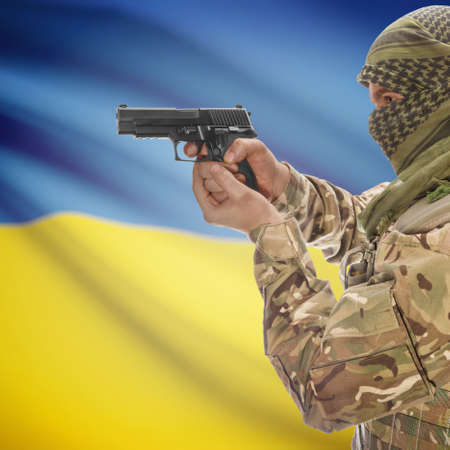 insurgency: Man with gun in hand and national flag on background series - Ukraine Stock Photo