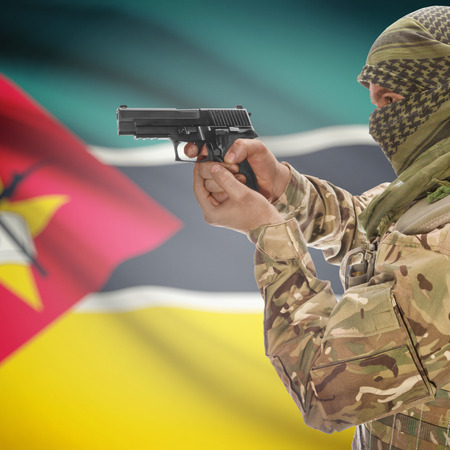 counterterrorism: Man with gun in hand and national flag on background series - Mozambique